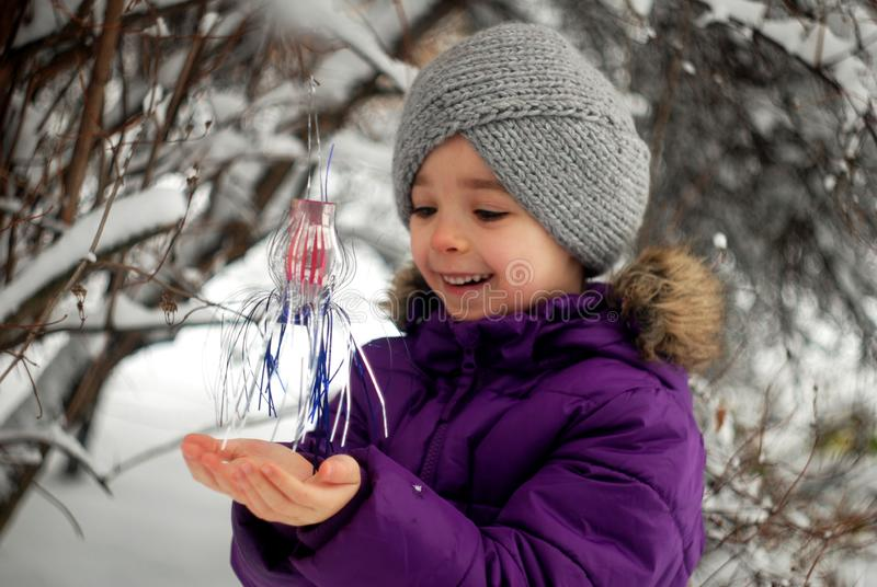 Girl hangs Christmas decoration on a tree in the garden royalty free stock photo