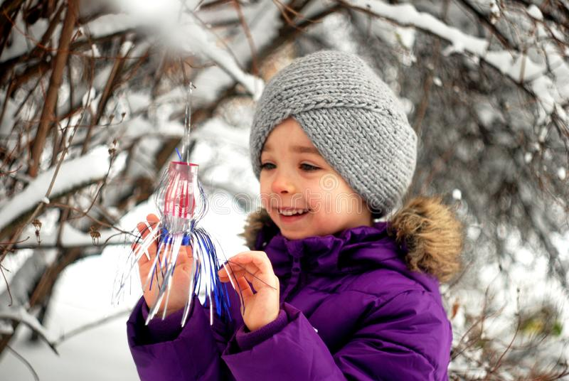 Girl hangs Christmas decoration on a tree in the garden royalty free stock photography