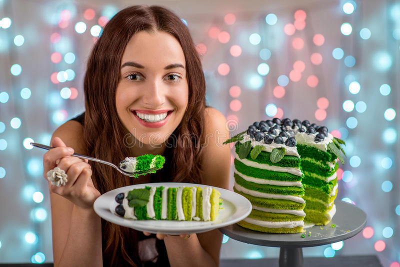 Girl with happy birthday cake. Beautiful girl tasting happy birthday cake on festive light background stock image
