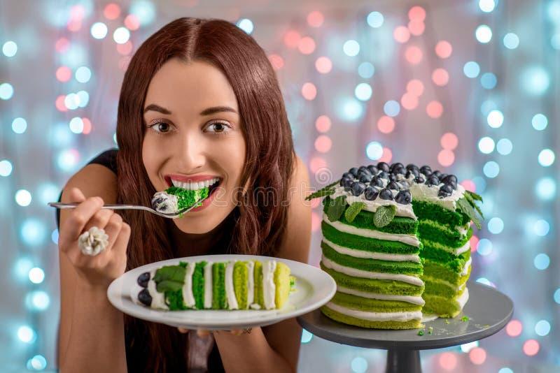 Girl with happy birthday cake. Beautiful girl tasting happy birthday cake on festive light background royalty free stock photography