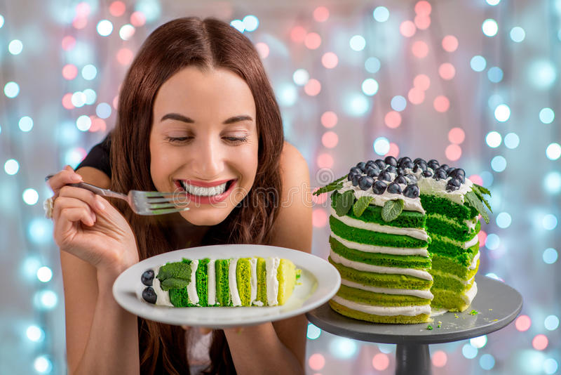Girl with happy birthday cake. Beautiful girl tasting happy birthday cake on festive light background stock photo