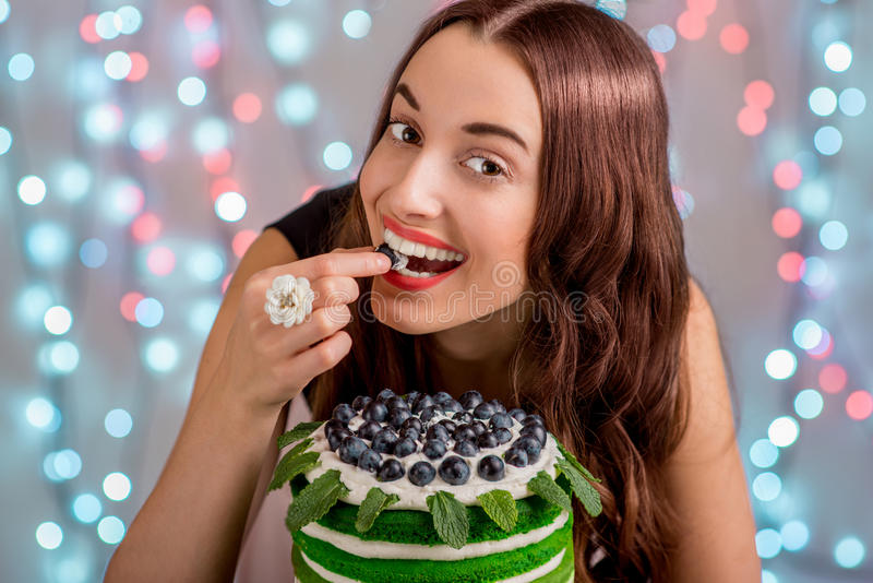 Girl with happy birthday cake. Beautiful girl with happy birthday cake tasting the grape on festive light background stock photography