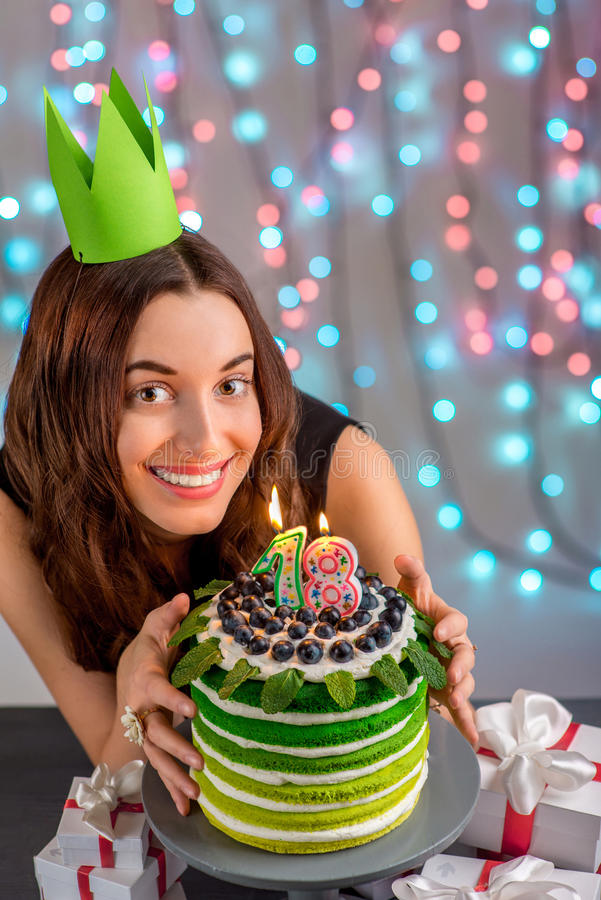 Girl with happy birthday cake. Eighteen girl with happy birthday cake on festive light background stock photo