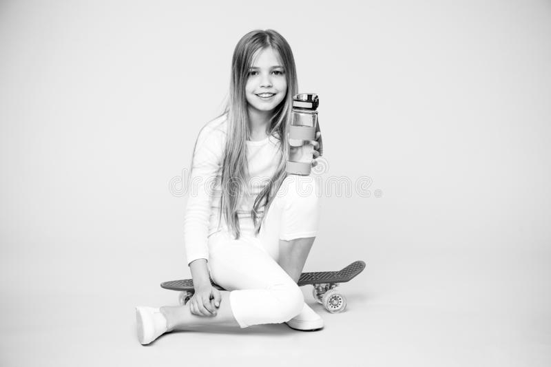 Girl happy face holds with water bottle while sit penny board pink background. Kid girl care body hydration. Active. Leisure and water balance. Active and stock images
