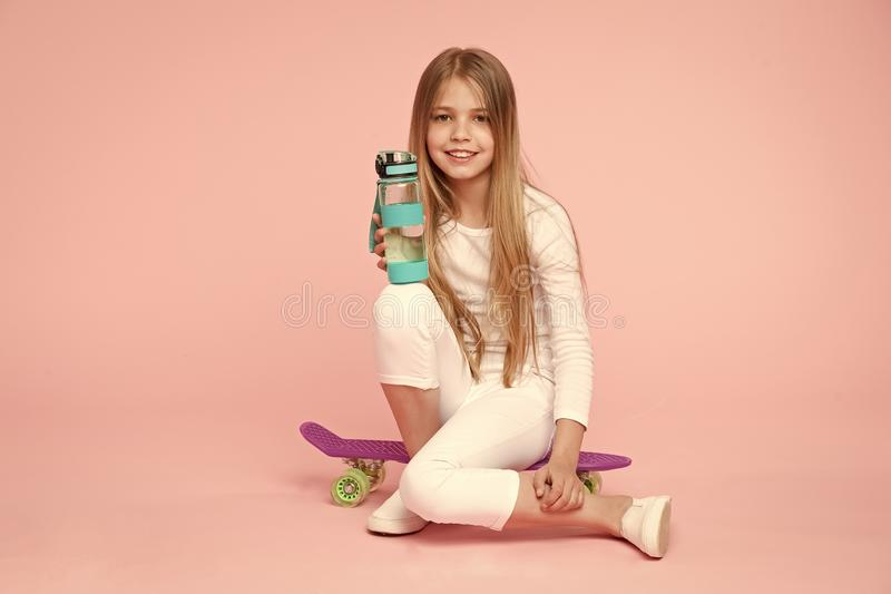 Girl happy face holds with water bottle while sit penny board pink background. Kid girl care body hydration. Active. Leisure and water balance. Active and royalty free stock images