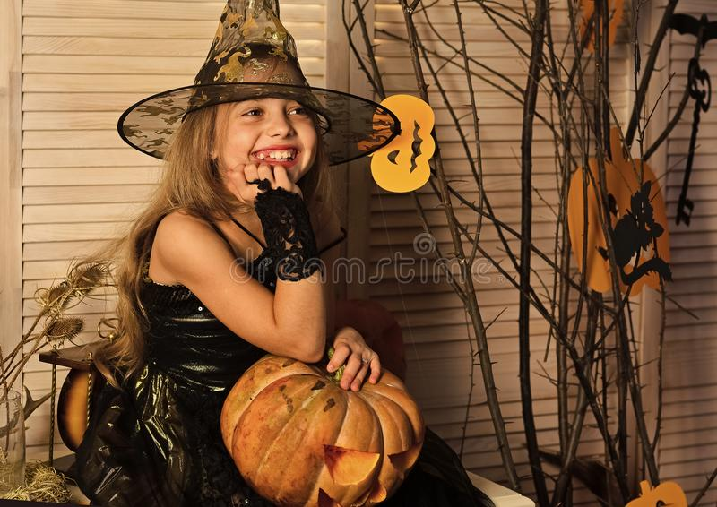 Girl with happy face on spooky carnival room background. Halloween party and celebration concept. Kid in witch hat and costume holds big jack o lantern. Little royalty free stock image