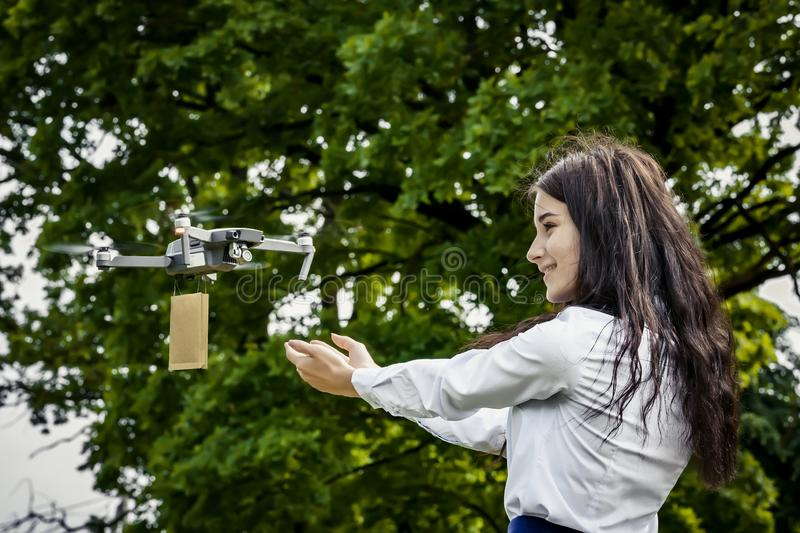The girl is happy with the gift delivered by the drone.  stock image