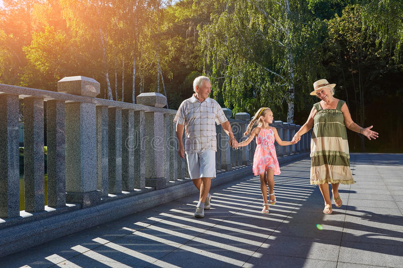Girl with happy grandparents outdoors. royalty free stock image