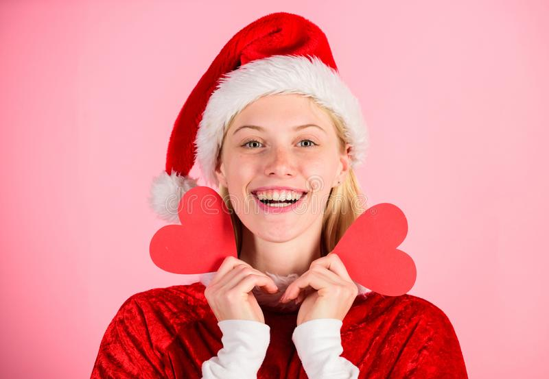 Girl happy wear santa costume celebrate christmas pink background. Merry christmas and happy new year. Woman hold heart. Symbol of love. Bring love to family royalty free stock photo