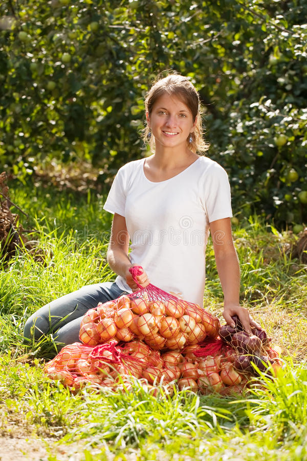 Girl with harvested onion. Young girl with harvested onion in field royalty free stock photography