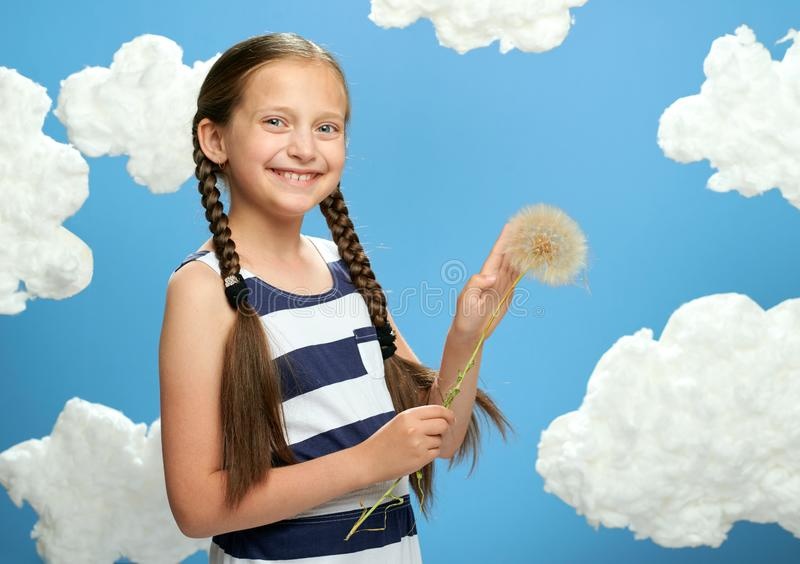 Girl has a big dandelion in her hands, dressed in striped dress, posing on a blue background with cotton clouds, the concept of su. Mmer, holiday and happiness stock image