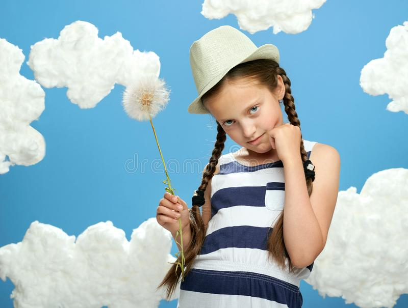 Girl has a big dandelion in her hands, dressed in striped dress, posing on a blue background with cotton clouds, the concept of su. Mmer, holiday and happiness stock photography