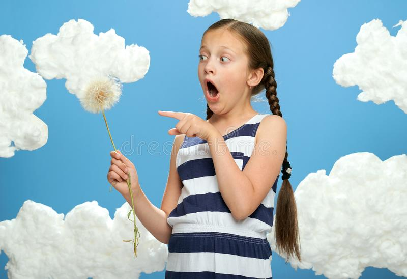 Girl has a big dandelion in her hands, dressed in striped dress, posing on a blue background with cotton clouds, the concept of su. Mmer, holiday and happiness royalty free stock photography