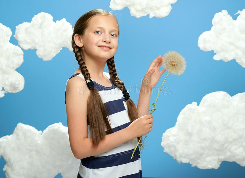 Girl has a big dandelion in her hands, dressed in striped dress, posing on a blue background with cotton clouds, the concept of su. Mmer, holiday and happiness stock photo