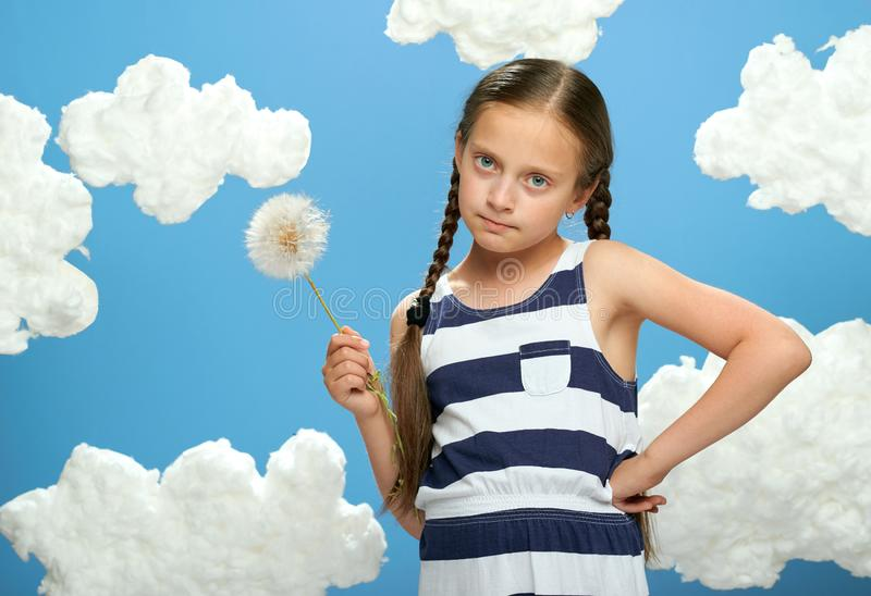 Girl has a big dandelion in her hands, dressed in striped dress, posing on a blue background with cotton clouds, the concept of su. Mmer, holiday and happiness royalty free stock photos