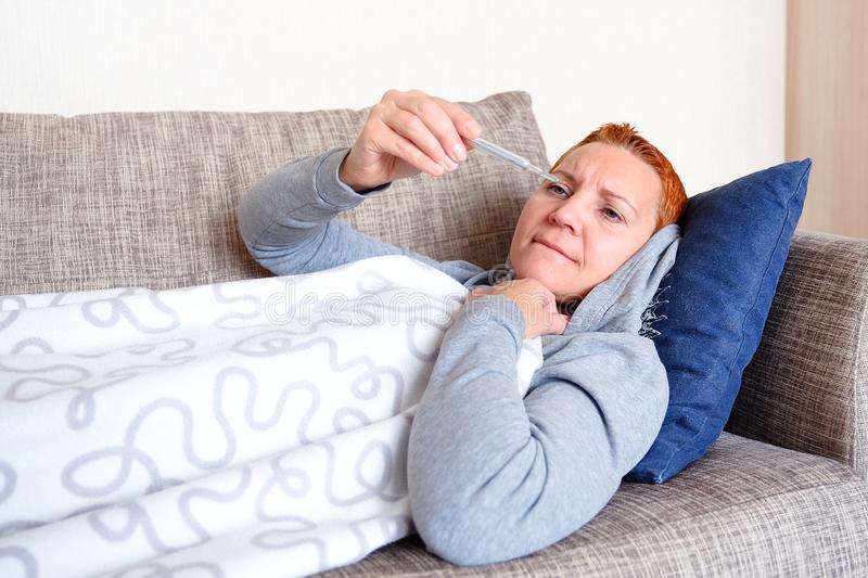 The girl has the flu. Lying in bed looking at the thermometer. Bad news. High temperature. Cold and flu. The concept of health. The girl has the flu. Lying in stock photos