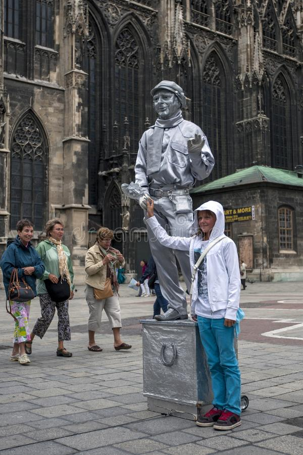A girl has her photograph taken with a statue street performer painted in silver in Vienna in Austria. stock photography
