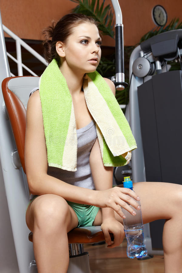 Girl has a rest. The girl with a bottle has a rest after exercises royalty free stock images