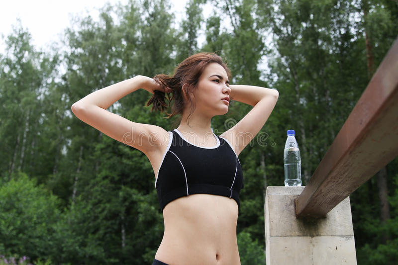 The girl has risen to take rest. The girl has risen to take rest after run in park stock image