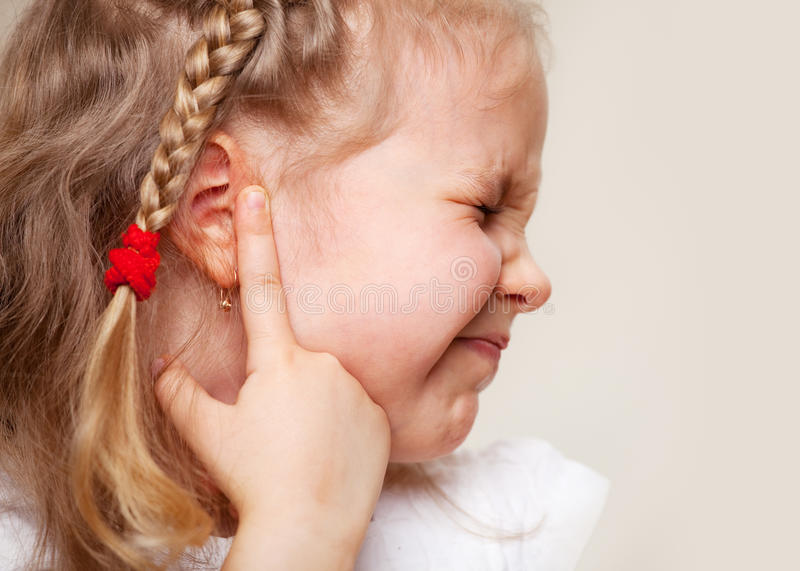 Girl has a sore ear. Child has a sore ear. Little girl suffering from otitis stock photos