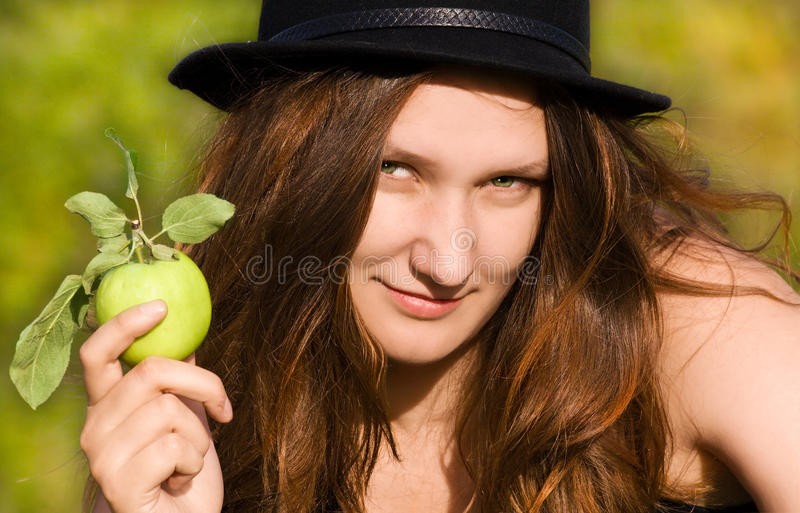 The girl in a hat with an apple royalty free stock image