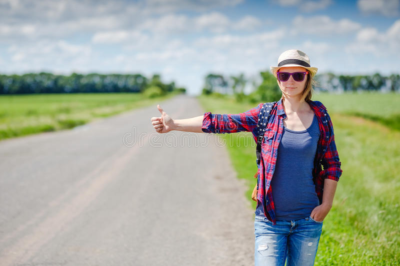 Girl with hat and backpack hitchhiking on the road. Girl with hat and backpack hitchhiking on the rural road stock images