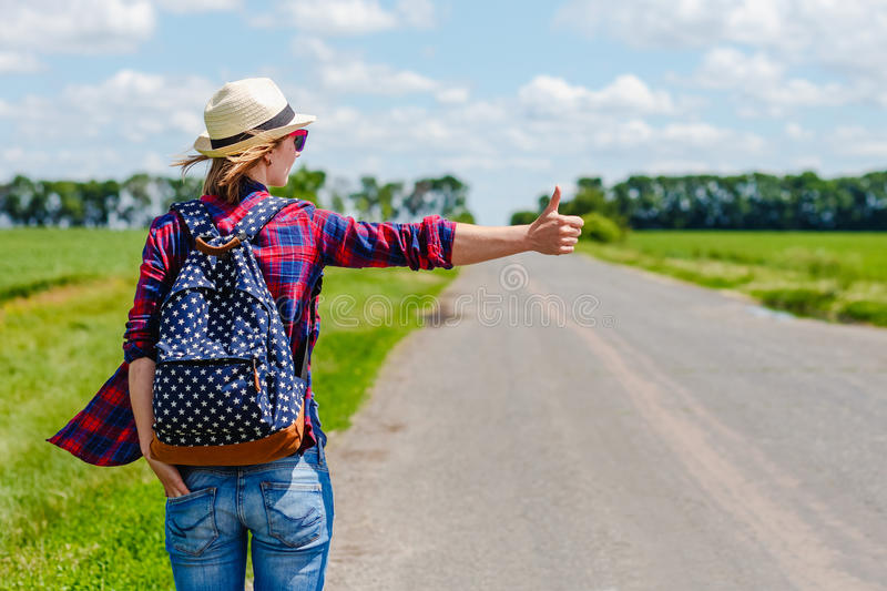 Girl with hat and backpack hitchhiking on the road royalty free stock images