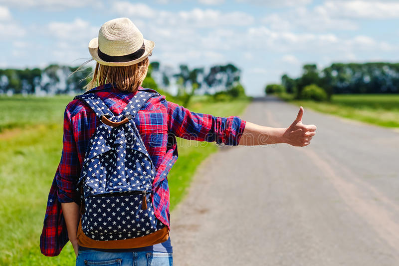 Girl with hat and backpack hitchhiking on the road stock image