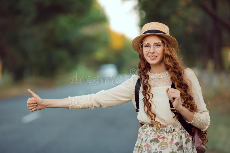 Girl with hat and backpack hitchhiking on the road. Hitchhiking tourism concept. Portrait of travel hitchhiker woman with hat and backpack walking on road during stock photo