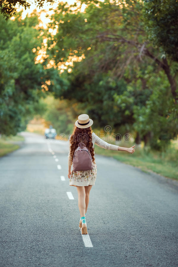 Girl with hat and backpack hitchhiking on the road royalty free stock image