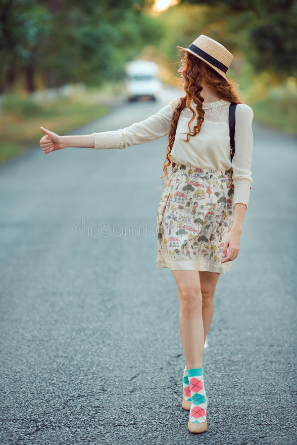 Girl with hat and backpack hitchhiking on the road. Hitchhiking tourism concept. Travel hitchhiker woman with hat and backpack walking on road during holiday royalty free stock photography