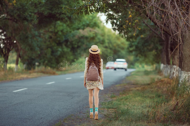 Girl with hat and backpack hitchhiking on the road. Hitchhiking tourism concept. Travel hitchhiker woman with hat and backpack walking on road during holiday royalty free stock photos