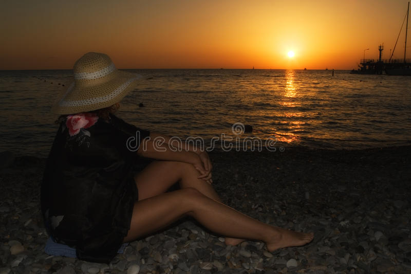 A girl in a hat with beautiful slender long legs watching the sunset on the sea. Human and nature stock photography