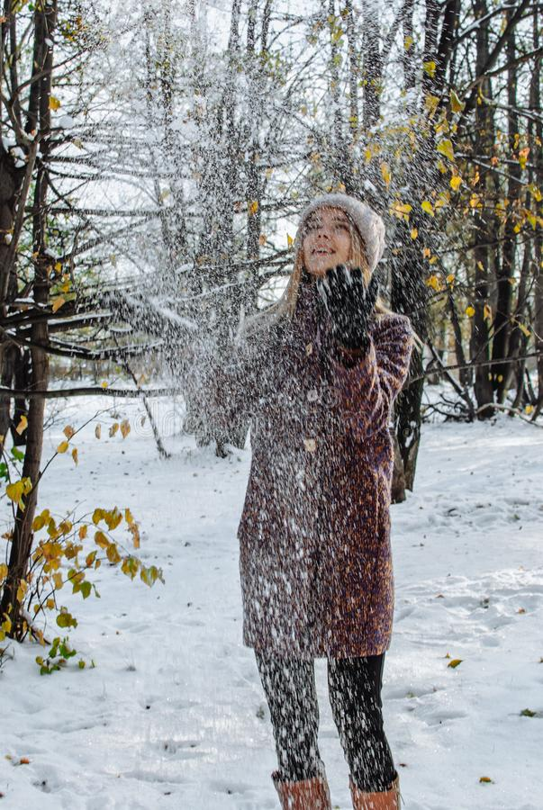 Girl enjoying first snow. Girl in hat and coat enjoying first snow in park royalty free stock photography