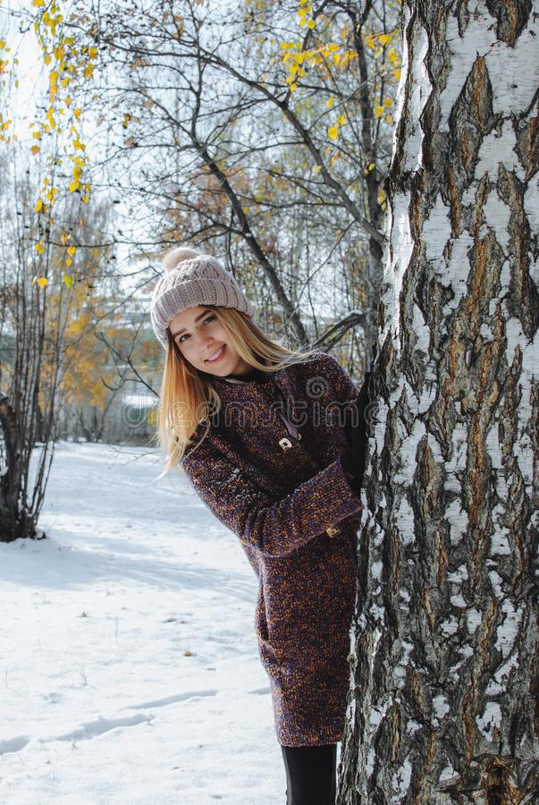 Girl enjoying first snow. Girl in hat and coat enjoying first snow in park stock image