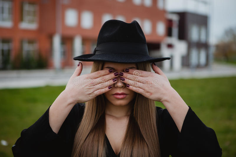Girl with a hat covering her face with the hands. Pretty stylish girl with a hat covering her face with the hands royalty free stock photography