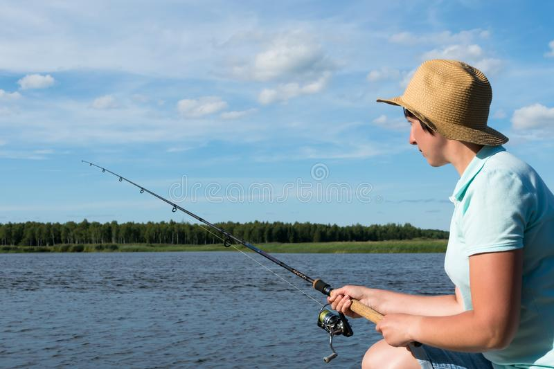 Girl with a hat is fishing on a spinning on the river in good weather, close-up stock photography