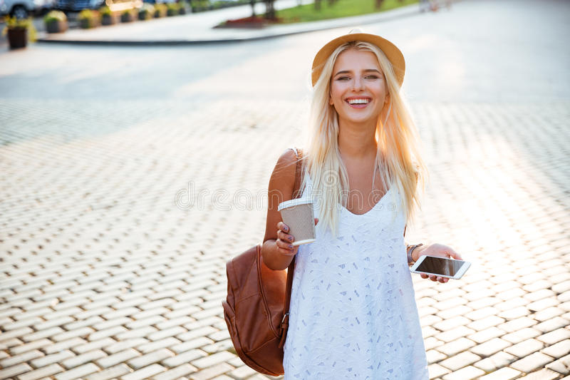 Girl in hat holding take away coffee cup and smartphone royalty free stock photography