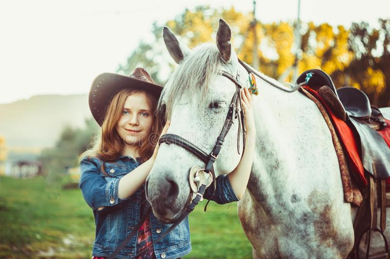 The girl in the hat on the horse. Young cowgirl on white horse smile in hat royalty free stock photo