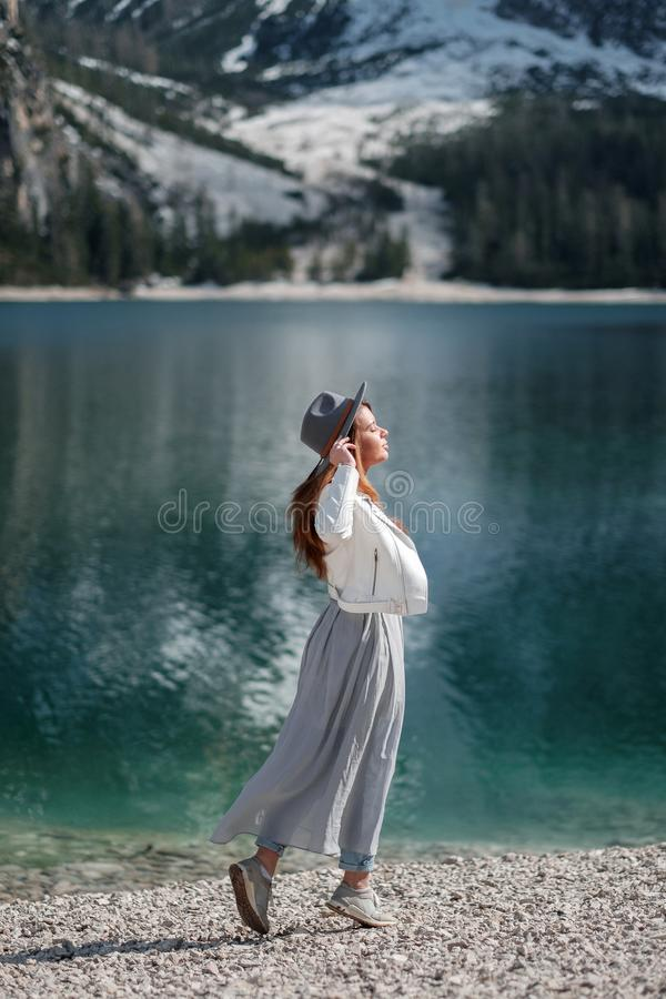A girl in a hat and a long dress is walking along the lake. Lago di Bries in the north of Italy royalty free stock images