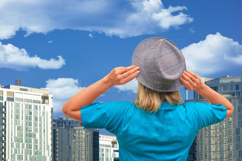 Girl in hat looks at on thick clouds and blue sky with skyscrapers or urban buildings on background. White middle aged woman stays royalty free stock photography