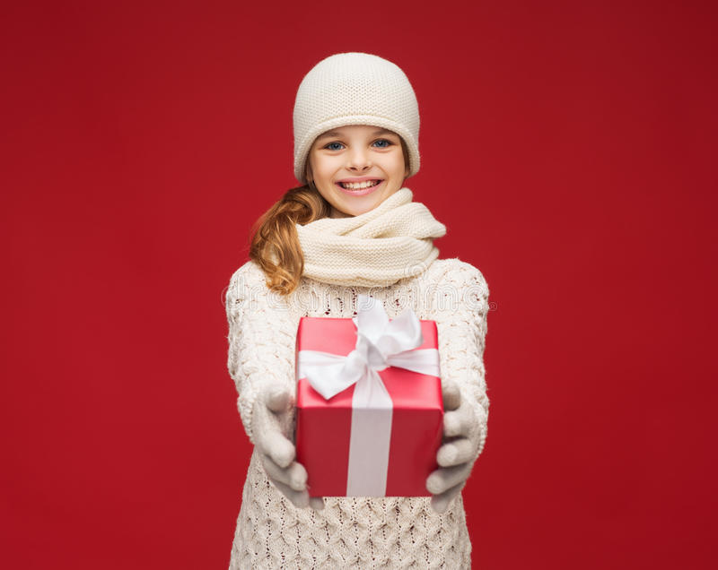 Girl in hat, muffler and gloves with gift box royalty free stock image