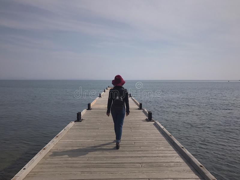 The girl in the hat on the pier royalty free stock images