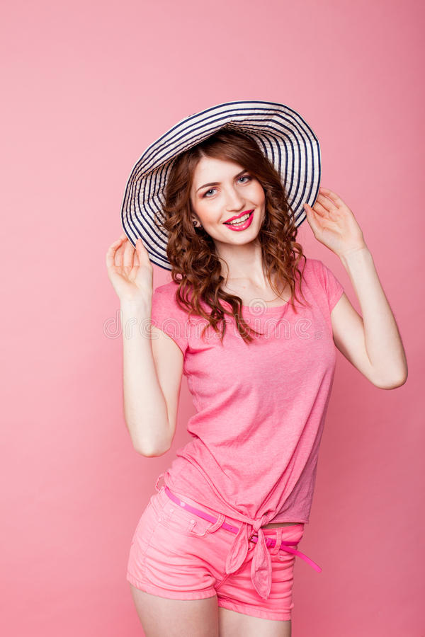 The girl in the hat on a pink background pinup royalty free stock image