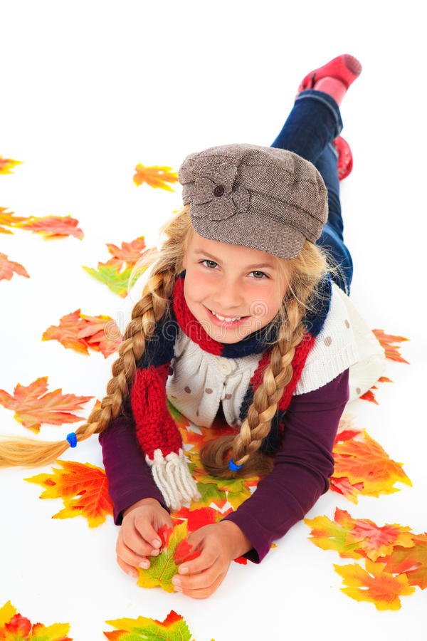 Girl with hat and scarf between autumn leaves