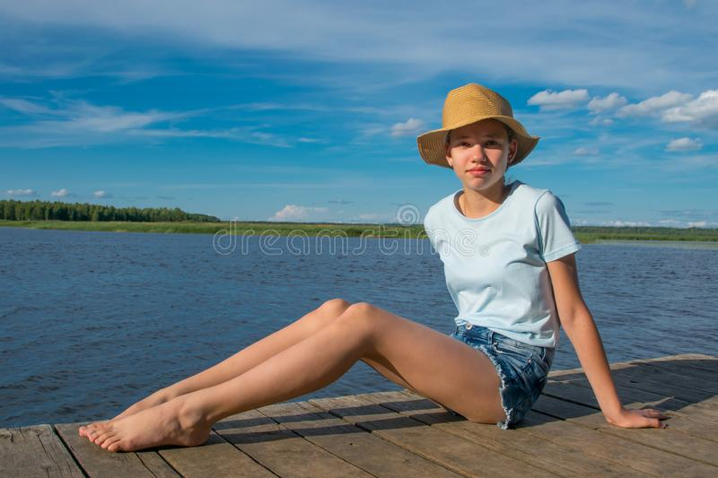 The girl in the hat sits on the pier, against the blue sky and the lake, gets a sun bath royalty free stock photo
