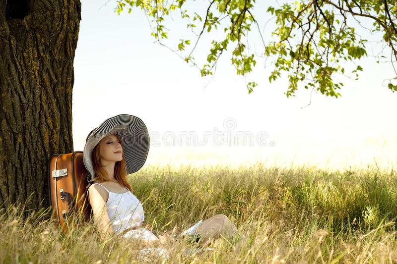 Girl In Hat Sitting Near Tree At Countryside. Stock Image