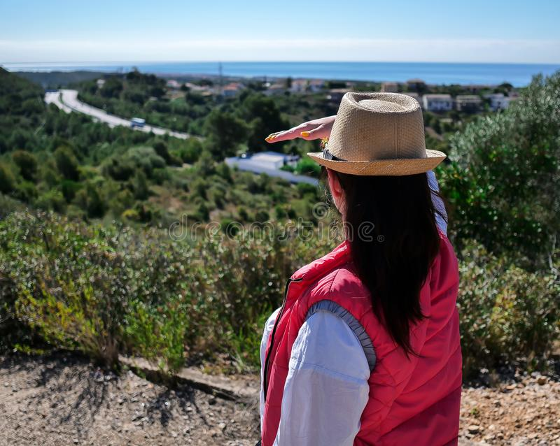 A brunette girl in a hat is standing on a mountain and looking at the road away stock photo