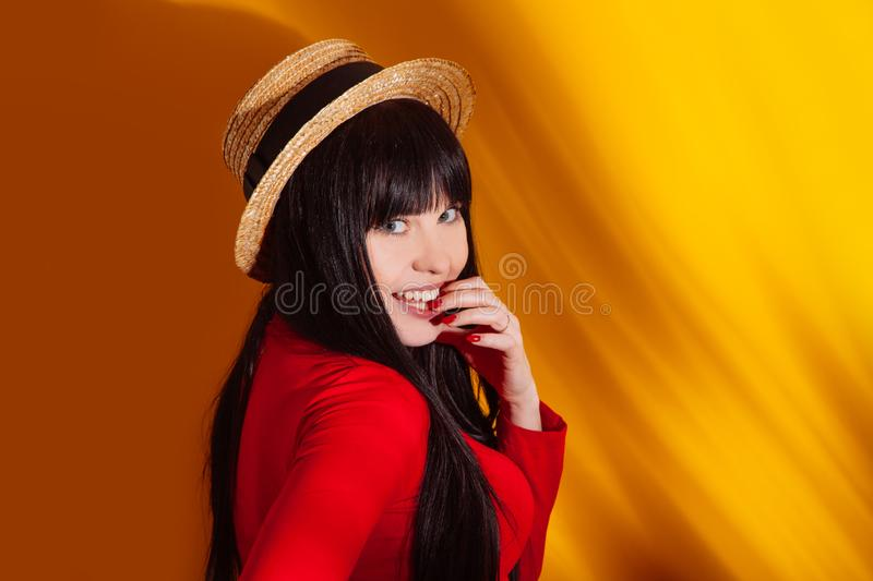 Girl hat sun light shadow tropical yellow orange young woman background red dress tropic royalty free stock photography