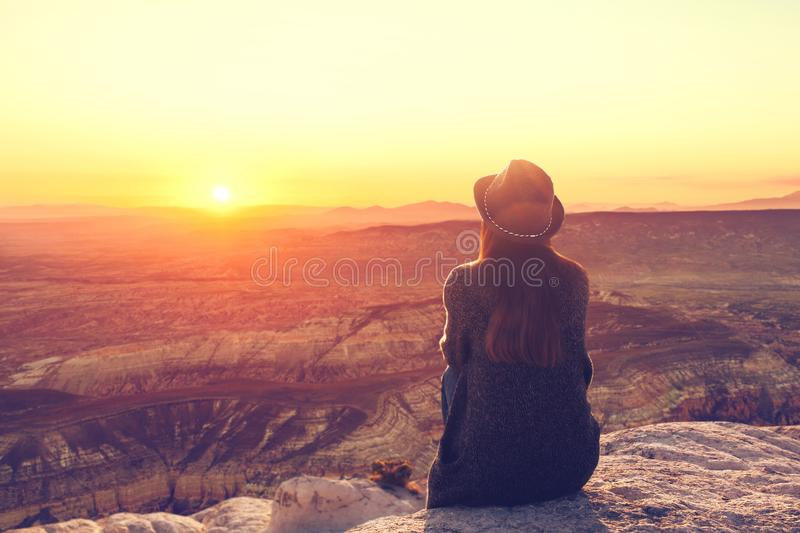 A view from the back of a girl in a hat sits on a hill and admires the beautiful view. A girl in a hat on top of a hill in silence and loneliness admires a royalty free stock photography